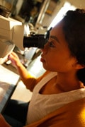 female Brandeis student looking looking a microscope in a lab