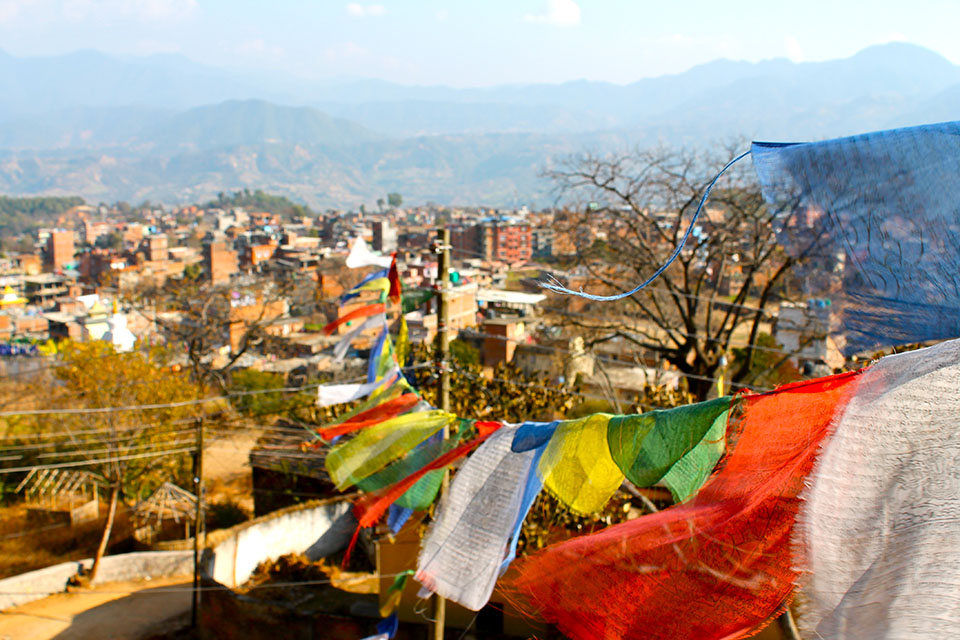 Prayer flags fly over a city in Nepal