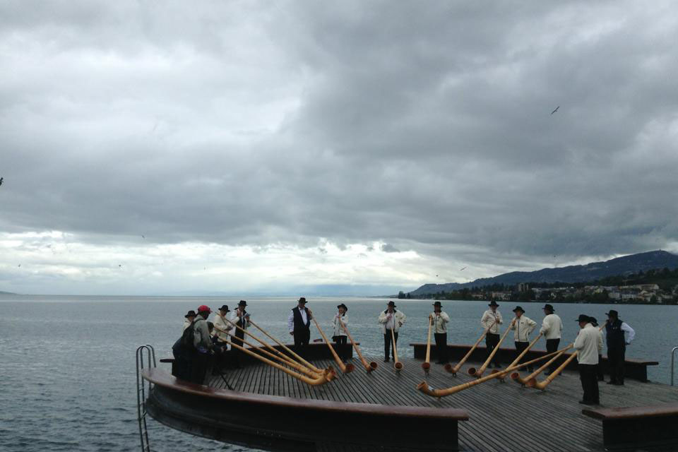 A group of men blowing alphorns in Switzerland