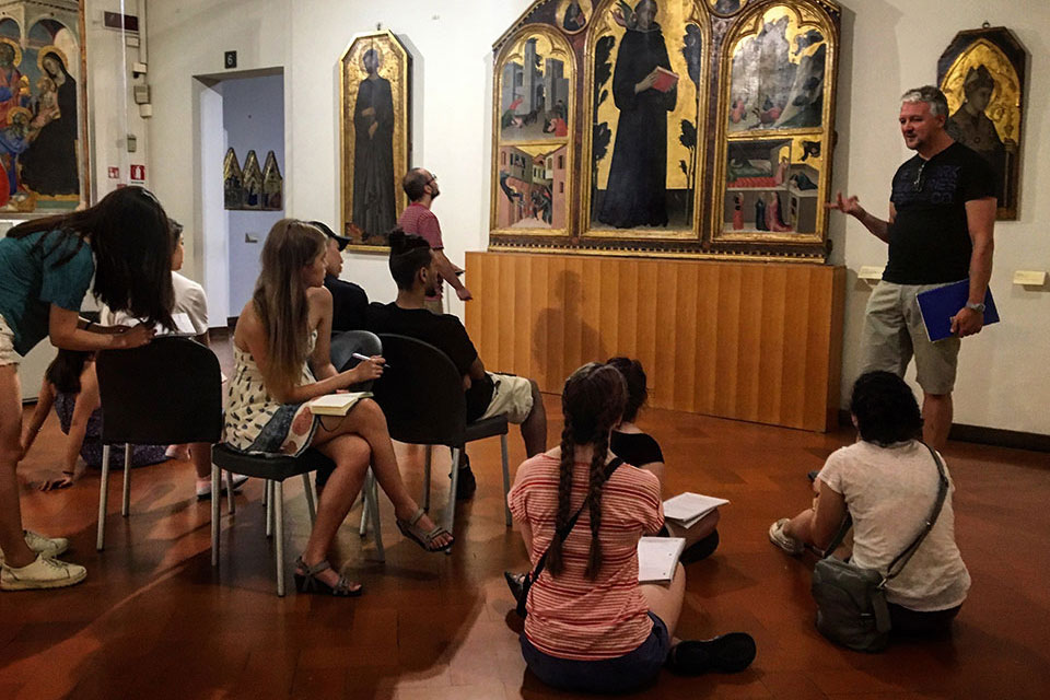 A group of students listens to a professor speak in an art museum
