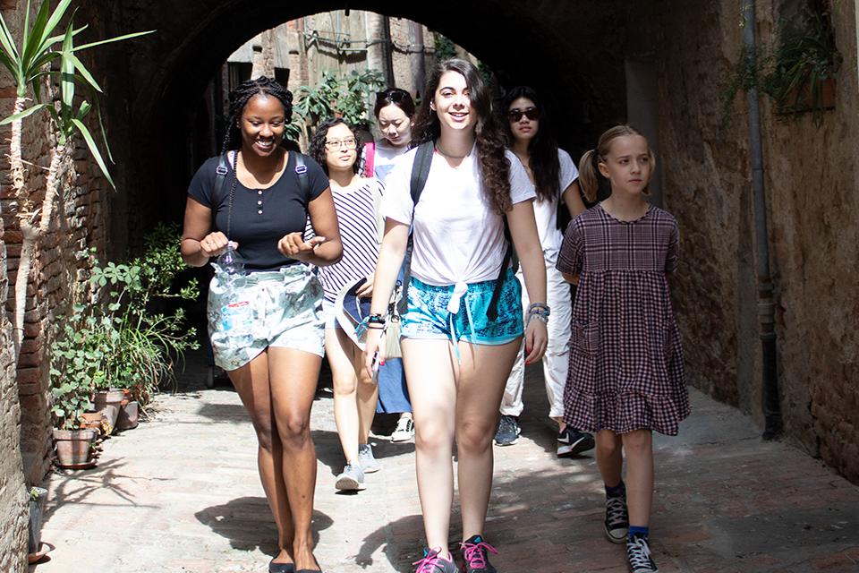 Students walking down an alleyway in Siena