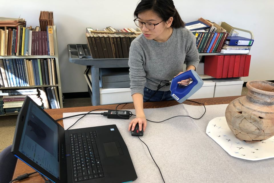 A student working on a 3D scan of an ancient vase