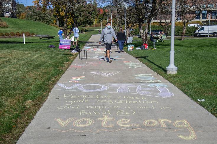 student walks down sidewalk that has slogans written in chalk