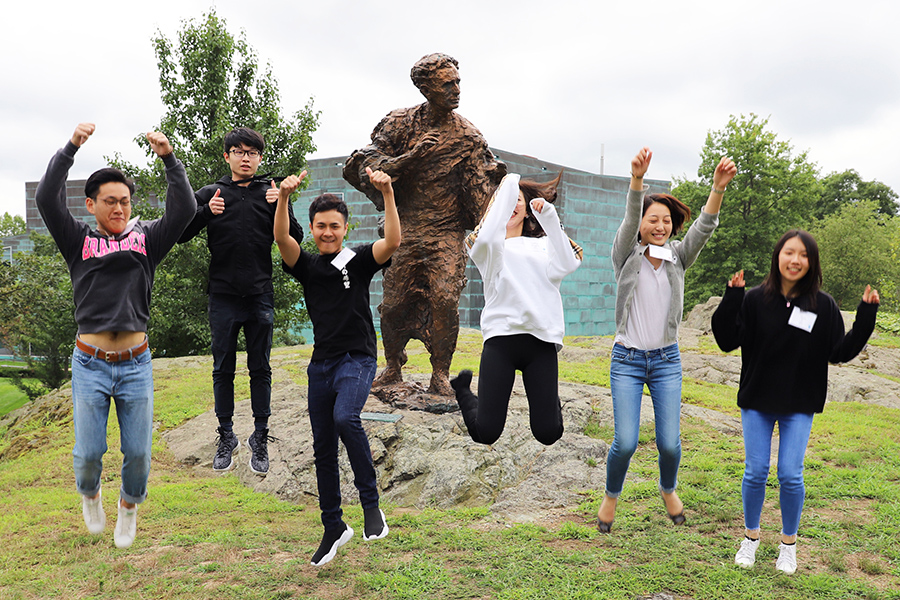 Students jump in front of a statue.