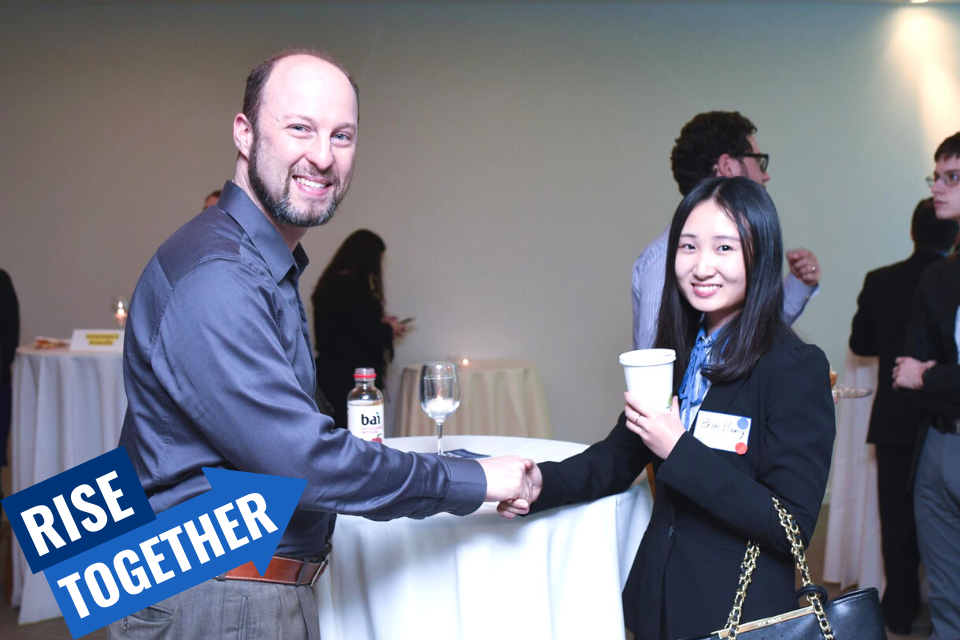 student and alum shaking hands at event