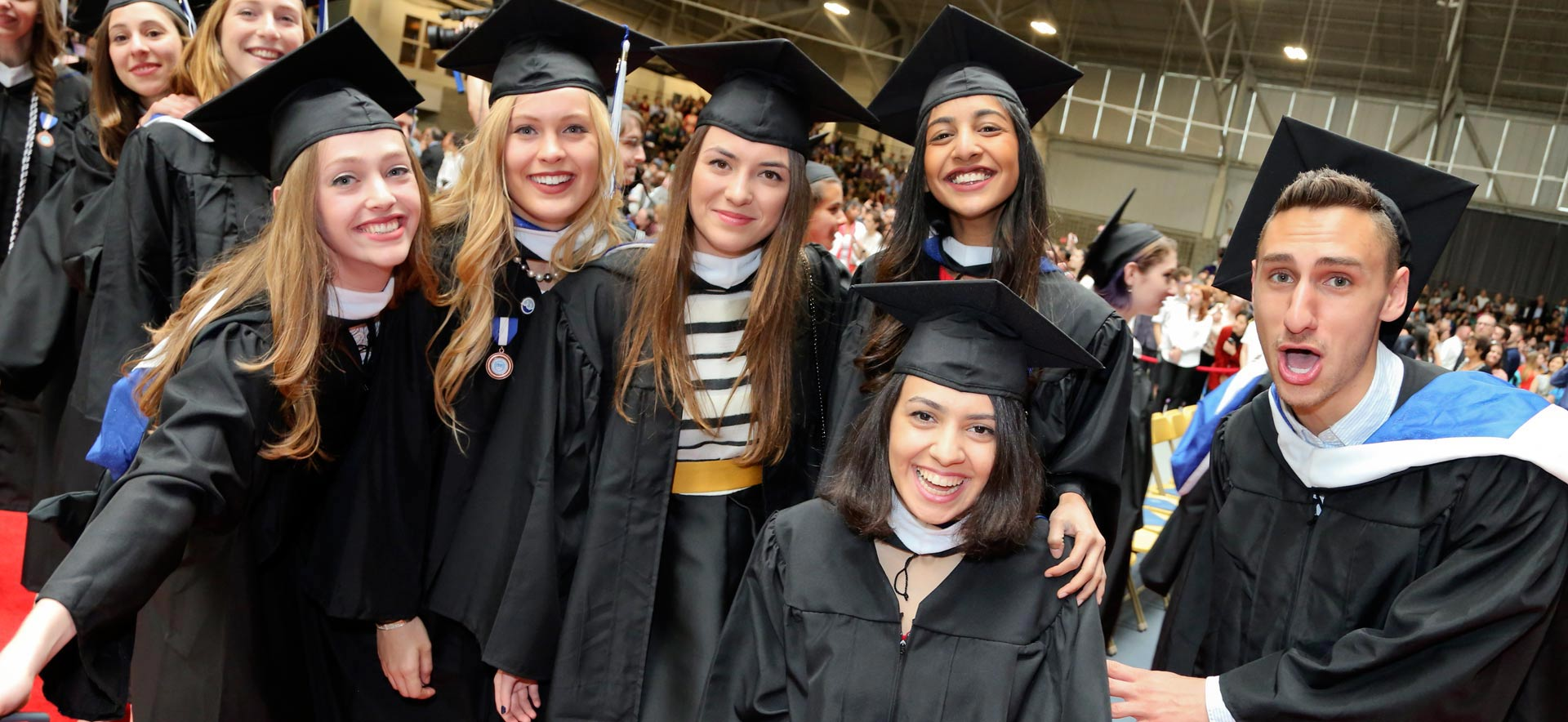 Male and female students wearing caps and gowns and smiling