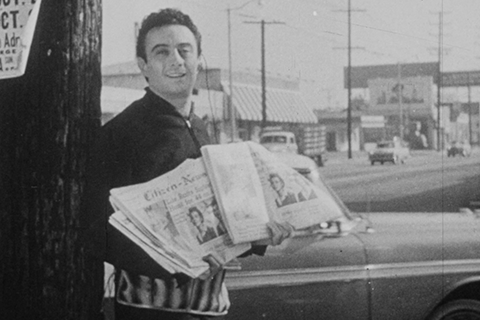 Black and white image of man holding newspapers