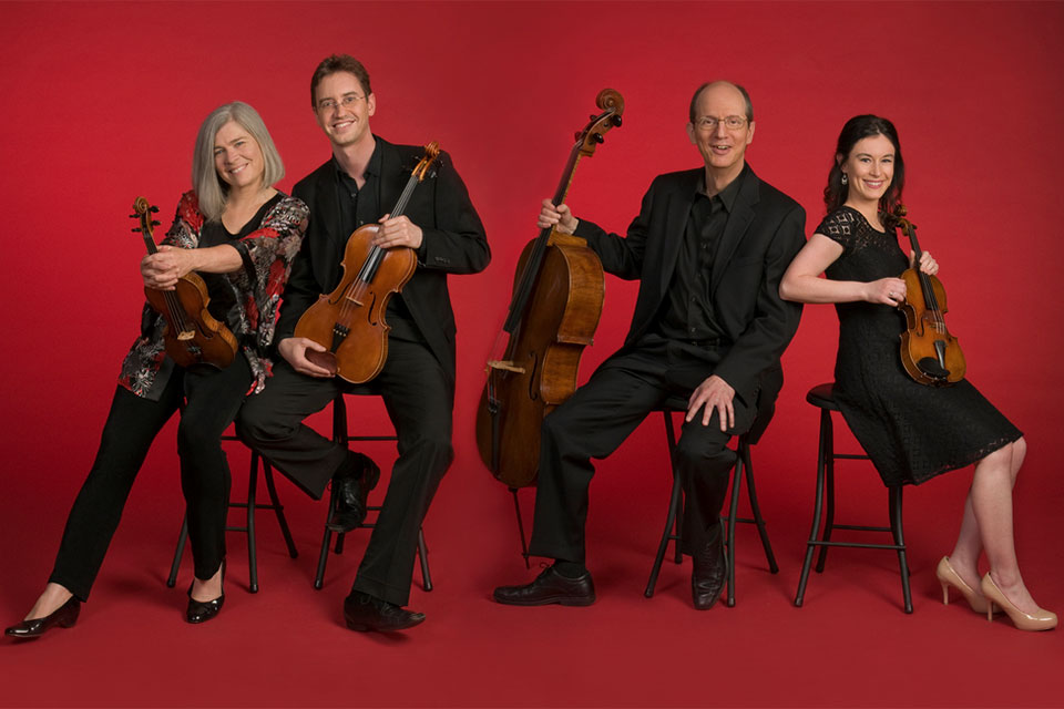 Portrait of the Lydian String Quartet with their instruments on a red background