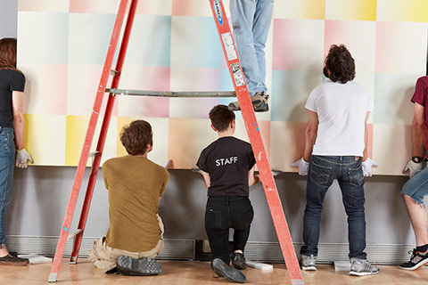 Rose Art Museum staff hang a painting on the wall
