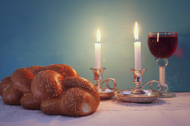 Challah, lit candles and wine on a table for Shabbat