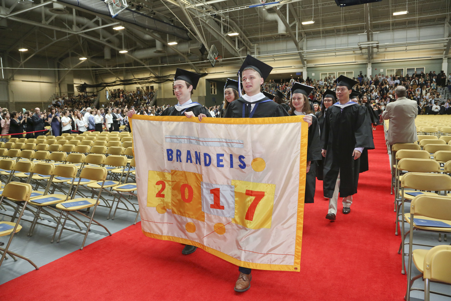 students in caps and gowns, holding a Brandeis 2017 banner, marching into Gosman Center for Commencement