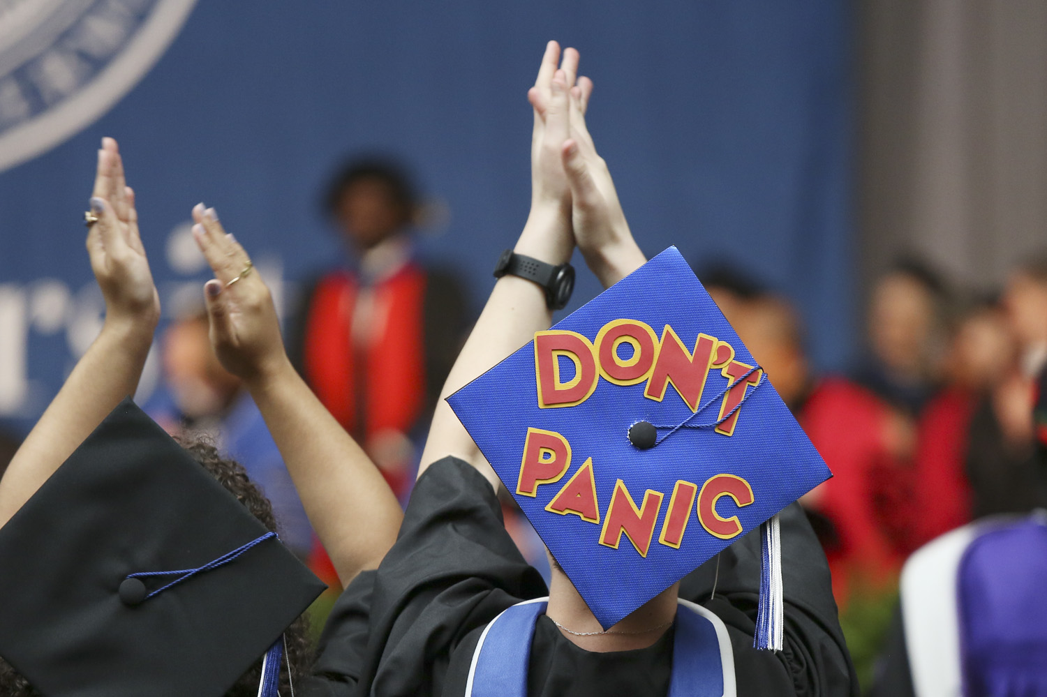 "A mortarboard decorated with red letters that read ""Don't Panic"""