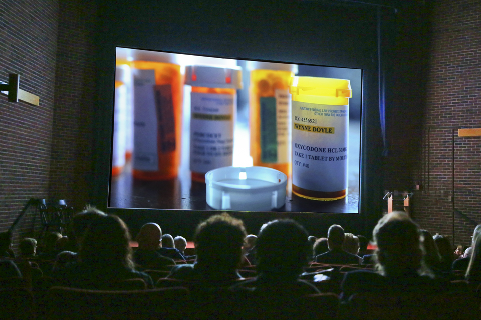 audience in darkened theater look at bottles of prescription painkillers, Ocycodone is the bottle in focus