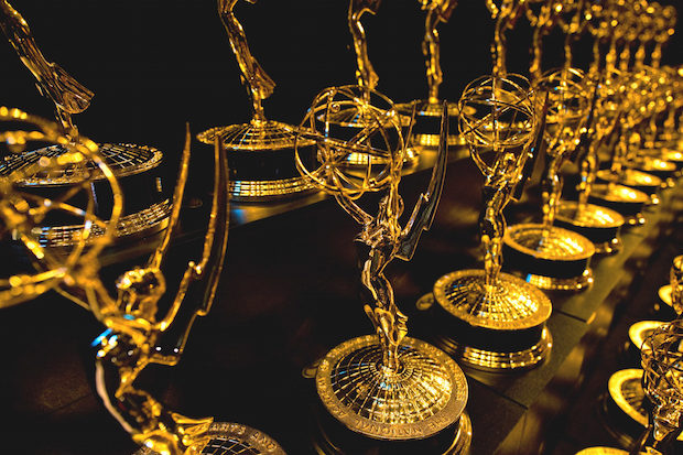 Dozens of Emmy Awards on a shelf