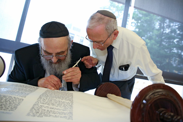 University professor Jonathan Sarna touches a quill being used by Rabbi Binyomin Spiro to finish a Torah scroll