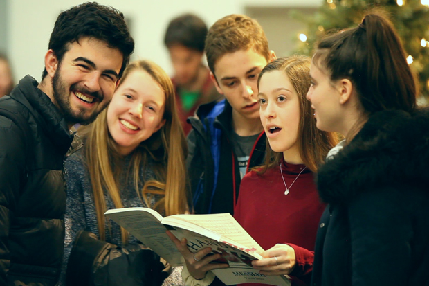 Students gathered around a songbook, smiling and singing