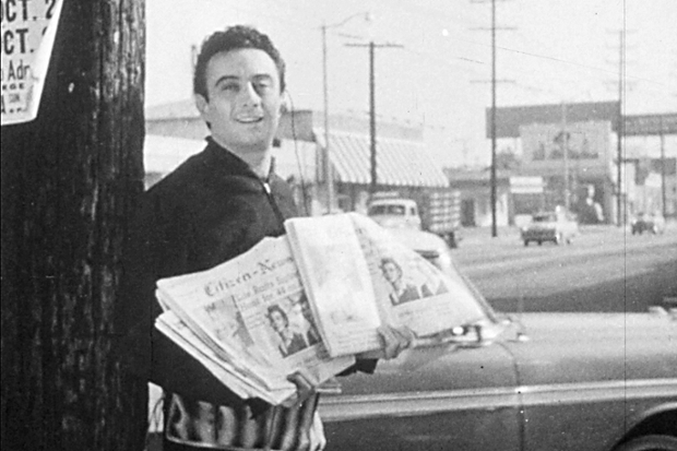 Lenny Bruce stands next to a tree holding newspapers in a black and white still from a film.