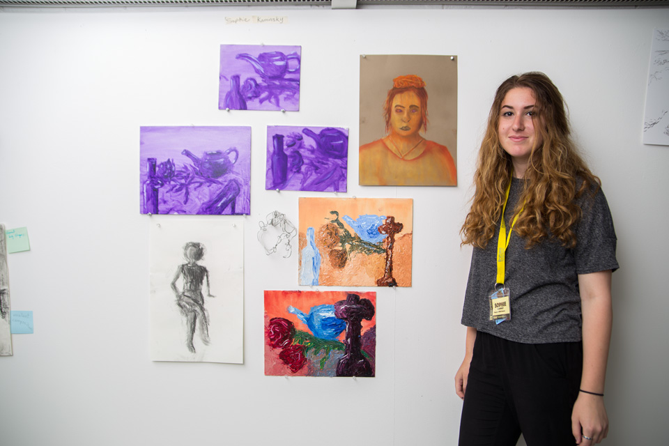 Sophie K. of Irvine, Calif, stands in front of sketches she made.