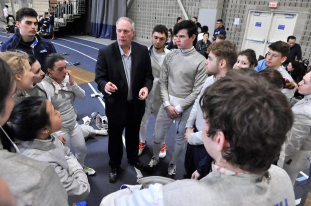 Brandeis fencing coach of 37 years Bill Shipman surrounded by fencers at a match
