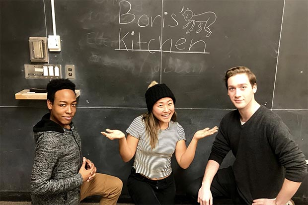 "3 people crouch in front of a blackboard that says ""Boris' Kitchen""."