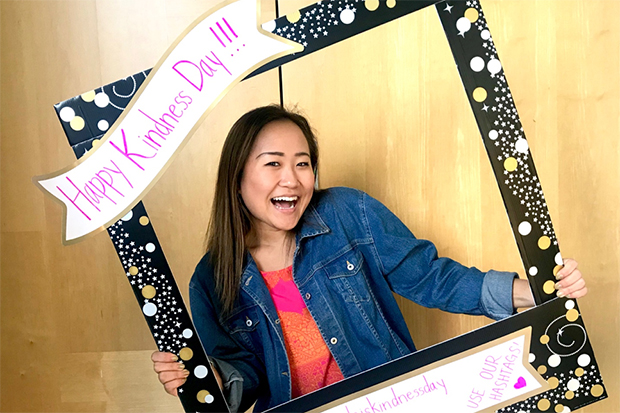 "A smiling Cho holds and peeks through a decorative black, gold and pink cardboard frame that reads ""Happy Kindness Day"" and ""Use our Hashtags"""