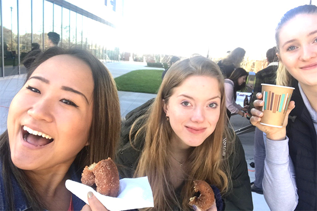 Cho takes a selfie with two other students. They are smiling and eating donuts.