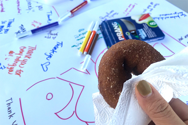 Closeup of a hand holding a cider donut in front of a poster board with colorful thank yous written over it.