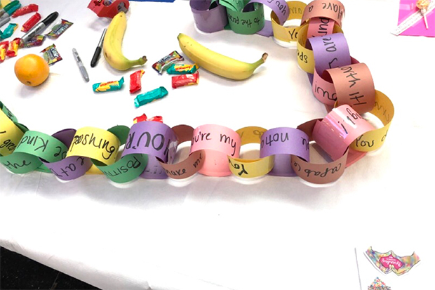A paper chain created with notes on the kindest thing someone has done for you lays on a table with fruit and candy.