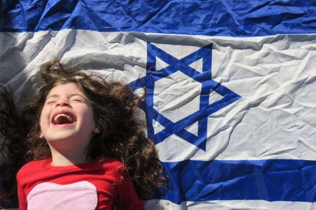 A little girl laughs in front of an Israeli flag