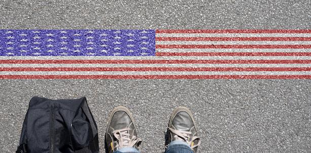 Feet near a line painted as an American flag on asphalt