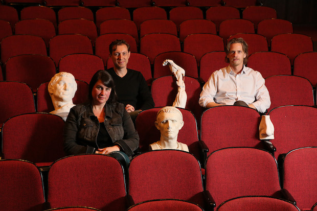 Cameron Anderson, Dmitry Troyanovsky and Joel Christensen sit in theater seats with ancient greek busts