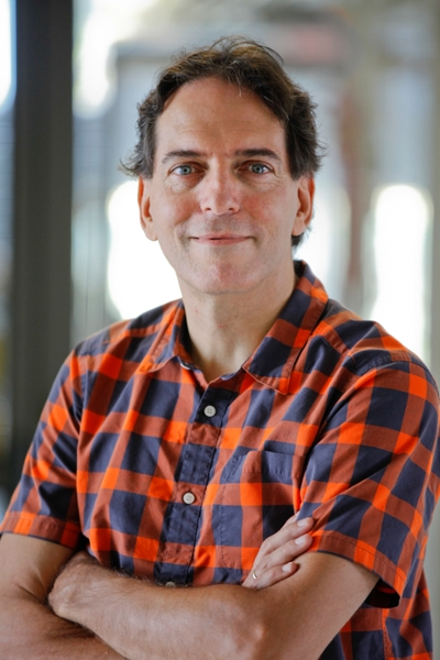 Jeff Gelles, professor of Biochemistry and Molecular Pharmacology, in a plaid shirt with arms folded