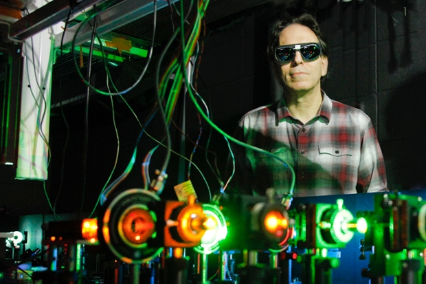 Jeff Gelles, professor of Biochemistry and Molecular Pharmacology, in a darkened room with wires connecting to red and green lights