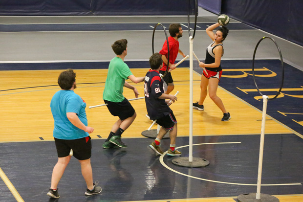 The Brandeis Quidditch team practices in Gosman. There are three vertical hoops and players hold sticks for brooms