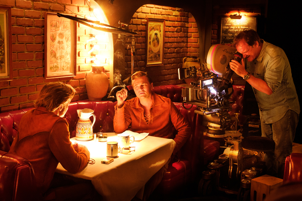 Film director Quentin Tarantino on a set filming Brad Pitt (back to camera) and Leonardo DiCaprio; they are sitting at a table in a red restaurant booth
