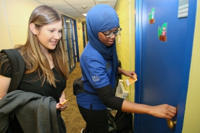 A DCL staffer lets a student into her residence hall room