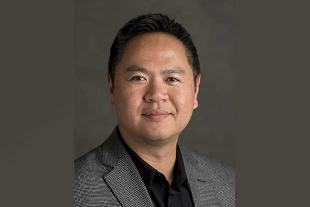 A headshot of Raymond Lu-Ming Ou, Vice Provost of Student Affairs, against a gray background