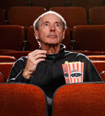 American studies professor Thomas Doherty seated in a theater eating popcorn