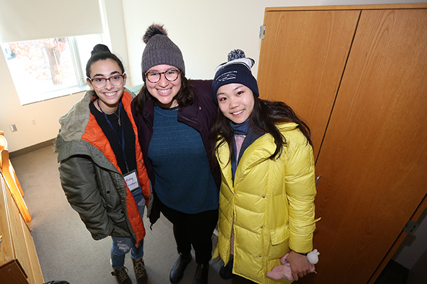three students standing in a residence hall on move-in day