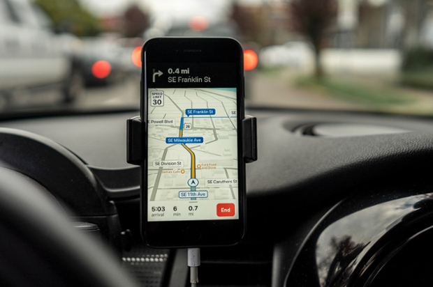 an iPhone mounted on a dashboard showing a map