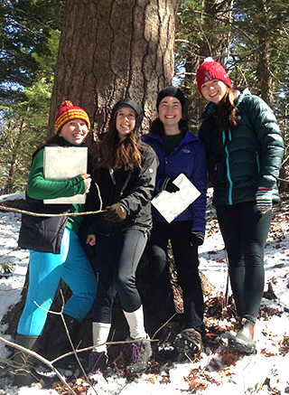 Four women students in winter coats and hats in front of a hemlock tree