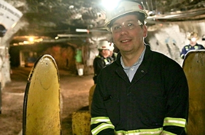 assistant professor of physics Bjoern Penning, wearing a hard hat and headlamp inside a former mine that is now the Sanford Underground Research Facility