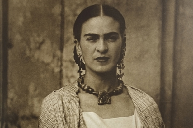 Sepia-tinted portrait of Frida Khalo, wearing large earings and a large necklace