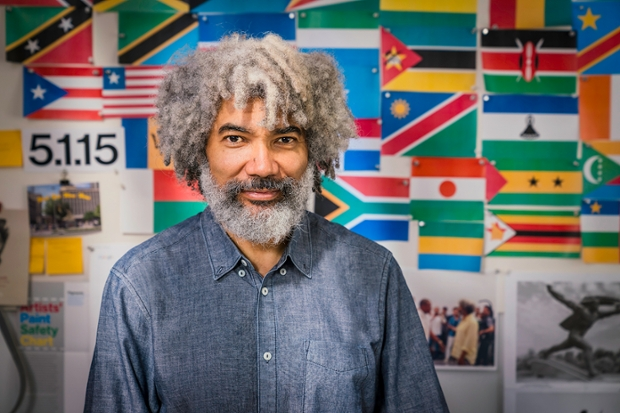 Artist Fred Wilson in front of a wall of flags and photographs