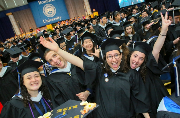A crowd of students celebrates graduation at Brandeis