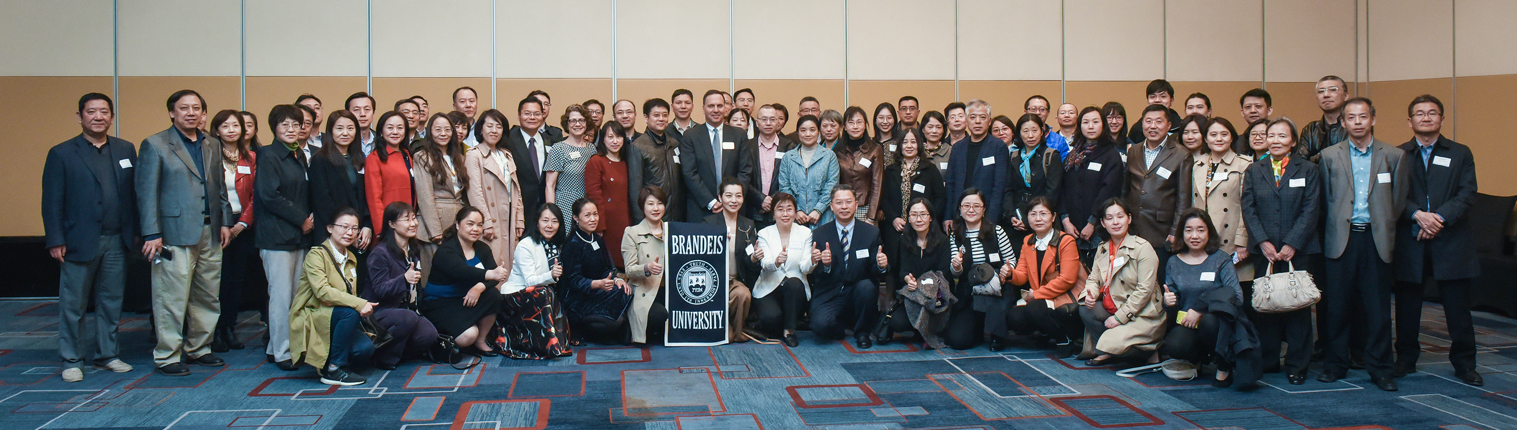 President Ron Liebowitz standing behind a Brandeis banner with several dozen parents of students in China