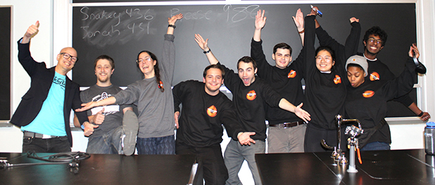 group of people dancing in front of a blackboard and behind a science table