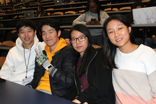 Four stidents sit in a lecture hall looking at camera - one wears a glove and gives a peace sign
