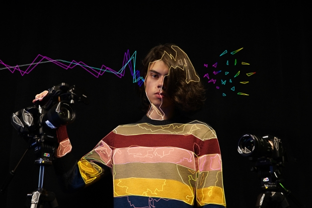 a digitally animated photo of Vicente Cayuela '22, wearing a striped sweater with two cameras against a black background