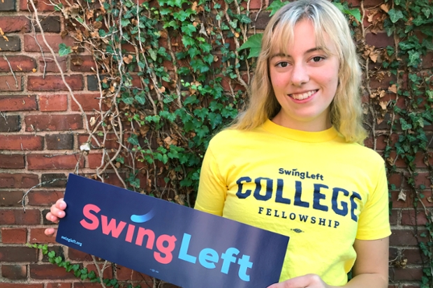 "Holly Newman '22, in a yellow t-shirt with a blue ""swing left"" bumpersticker, standing in front of an ivy-covered brick wall"